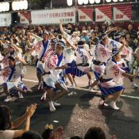 Block party: The Shin-Nonki troupe of dancers entertain a crowd on the street near Koenji Station in Tokyo.   JAMES HADFIELD