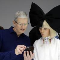 Apple CEO Tim Cook shows an iPhone 7 to performer Maddie Ziegler during an event to announce new products, Wednesday in San Francisco. | AP