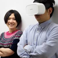 Yuka Kojima poses with a model wearing a Fove eye-tracking virtual reality headset in Tokyo on Sept. 20. | BLOOMBERG