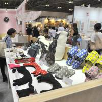 Visitors peruse the giant collection of cat-themed goods during the 82nd Tokyo International Gift Show at Tokyo Big Sight in Koto Ward on Thursday. | YOSHIAKI MIURA