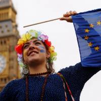A pro-Europe demonstrator waves a flag in London on Saturday during a March for Europe protest against Britain's decision in June to exit the European Union. Japan has warned that the decision could prompt Japanese financial institutions to relocate from London. | REUTERS