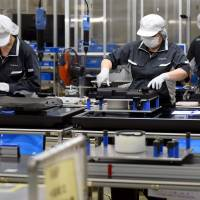 Workers assemble analog record players on an assembly line at Panasonic's Utsunomiya plant in Tochigi Prefecture on Wednesday. | AFP-JIJI