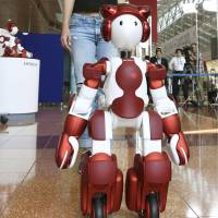 Hitachi Ltd's EMIEW3 humanoid robot guides a woman during a demonstration at Tokyo's Haneda airport on Friday. | KYODO