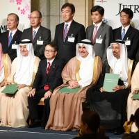 Trade minister Hiroshige Seko is flanked by members of a Saudi delegation in Tokyo on Thursday. Japanese company executives stand behind them. | KYODO