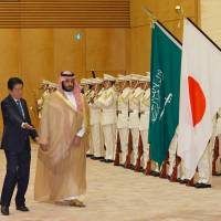 Prime Minister Shinzo Abe escorts visiting Saudi Arabia's Deputy Crown Prince Mohammed bin Salman as they review a guard of honor prior to their meeting at Abe's office in Tokyo on Thursday. | AFP-JIJI