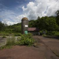 An abandoned building stands at the Coal History Village in the town of Yubari, Hokkaido, on July 21. The bankrupt former mining town is urging its shrunken population to resettle toward its center. | BLOOMBERG