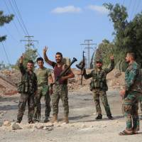 Forces loyal to Syria's President Bashar Assad flash victory signs as they stand at a military complex, after they recaptured areas in southwestern Aleppo on Sunday that rebels had seized last month in Syria in this handout picture provided by SANA on Monday. | SANA / HANDOUT VIA REUTERS