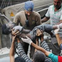 A Civil Defense worker carryies the body of a child after airstrikes hit al-Shaar neighborhood in Aleppo, Syria, Tuesday.  | SYRIAN CIVIL DEFENSE WHITE HELMETS VIA AP
