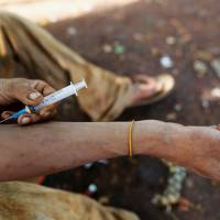 A man injects heroin into his arm along a street in Man Sam, northern Shan state, Myanmar, July 11. | REUTERS