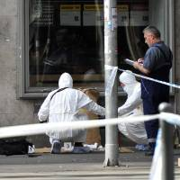 Police forensic experts examine the scene in central Budapest Sunday after an explosion of yet unknown origin occured in a shop late Saturday night. According to an expert, apparently a home made bomb went off in front of the shop. The explosion injured two patrolling policemen. | PETER LAKATOS / MTI VIA AP