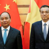 Chinese Premier Li Keqiang (right) and Vietnamese Prime Minister Nguyen Xuan Phuc attend a signing ceremony at the Great Hall of the People in Beijing on Tuesday. | REUTERS