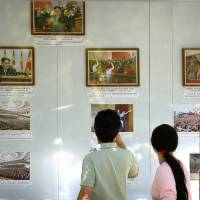 People look at a display of photos outside the North Korean Embassy in Beijing on Friday after North Korea conducted a 'higher-level' nuclear warhead test.   AP