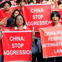 Filipino and Vietnamese activists display placards during a rally over their South China Sea disputes in front of a Chinese Consulate in Makati city, Metro Manila, on Aug. 6. | REUTERS