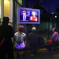People watch the first debate between Hillary Clinton and Donald Trump at an office building in Hollywood on Monday. | AFP-JIJI