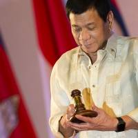 Philippine President Rodrigo Duterte holds the gavel during the closing ceremony of the Association of Southeast Asian Nations and handover of the ASEAN chairmanship to the Philippines in Vientiane last Thursday. | AFP-JIJI