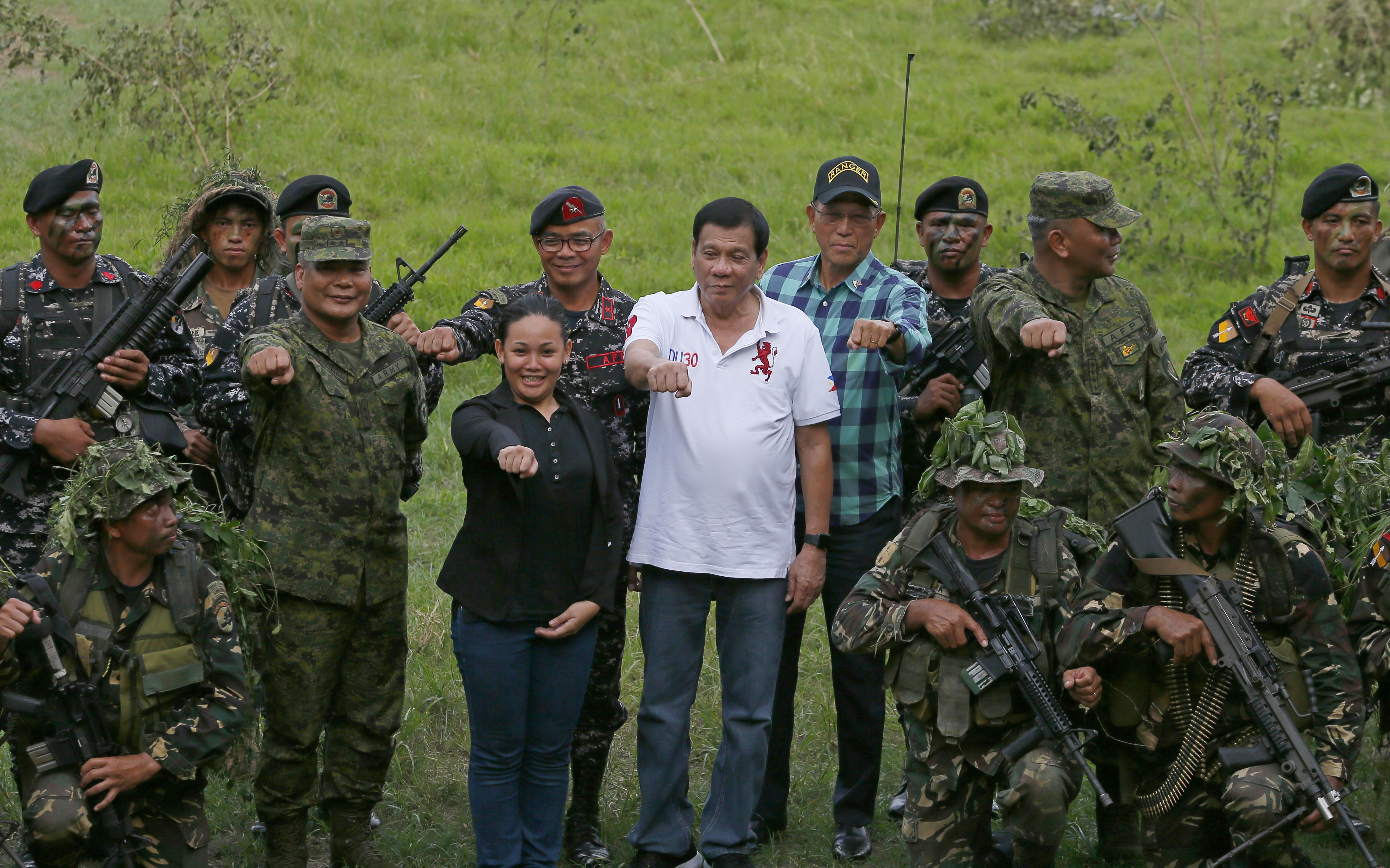 President Rodrigo Duterte (in white shirt) is seen with Philippine Army Scout Rangers on Thursday at their headquarters at Camp Tecson, north of Manila. | AP