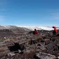 In this photo provided by Laure Gauthiez, taken in July 2012, a field team examines rocks in Greenland.   LAURE GAUTHIEZ / THE AUSTRALIAN NATIONAL UNIVERSITY VIA AP