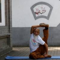 Li Liangui shows off his 'suogugong' kung fu skills at a park in Beijing on June 30. | REUTERS