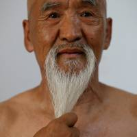 Li Liangui touches his beard as he demonstrates 'suogugong' kung fu skills for the camera at his apartment in Beijing on July 2. | REUTERS