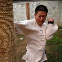 Kung fu master Xing Xi is seen practicing at his academy in Beijing on June 29. | REUTERS