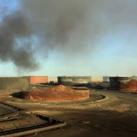 Smoke billows in January from a petroleum storage tank after a fire was extinguished following fighting at Al-Sidra oil terminal, near Ras Lanuf in the so-called 'oil crescent' along Libya's northern coast. Forces loyal to Gen. Khalifa Haftar on Sunday said they had seized the Al-Sidra and Ras Lanuf oil export terminals as the Tripoli-based Government of National Accord (GNA) struggles to assert its authority over the oil-rich country. | AFP-JIJI
