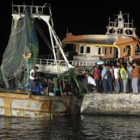 People gather on the quay as the wreck of a migrant boat raised by the Egyptian navy and maritime rescuers arrives in the Egyptian port city of Rosetta on Tuesday. The Egyptian military said 163 people had been rescued. The boat would have had at least 365 people on board when it went down en route to Italy, according to official figures. | AFP-JIJI