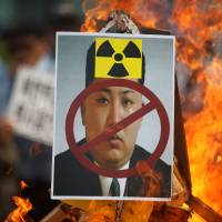 A poster featuring North Korean leader Kim Jong Un is set on fire during an anti-North Korea rally in central Seoul on Saturday. | REUTERS