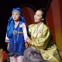 A North Korean woman and her son take part in the 14th National Korean Dress Show in Pyongyang, in a photo released Wednesday.   AFP-JIJI