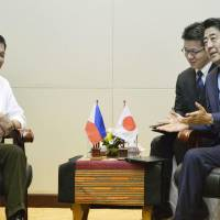 Prime Minister Shinzo Abe discusses the South China Sea and other issues with Philippine President Rodrigo Duterte Tuesday in the Laotian capital of Vientiane. | KYODO