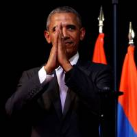 U.S. President Barack Obama holds his hands together and bows at the end of his speech on the sidelines of the ASEAN summit in Vientiane on Tuesday. | REUTERS