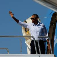 U.S. President Barack Obama on Wednesday boards Air Force One at Reno-Tahoe International Airport in Reno, Nevada, to depart for Hawaii, on his way to tour Midway Atoll and attend summits in Laos and China. | REUTERS