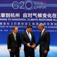 U.S. President Barack Obama moves to shake hands with Chinese President Xi Jinping (center) and U.N. Secretary-General Ban Ki-moon during a ceremony marking the joint ratification of the Paris climate change agreement at the West Lake State Guest House in Hangzhou, China, on Saturday.   REUTERS