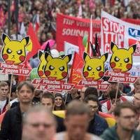 Demonstrators hold up posters reading, 'Pikachu, too, is against TTIP' during a protest against the massive trans-Atlantic trade deals CETA and TTIP on Saturday in Frankfurt am Main, Germany. | AFP-JIJI