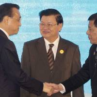 Chinese Premier Li Keqiang (left) shakes hands with Philippine President Rodrigo Duterte as Laotian Prime Minister Thongloun Sisoulith watches during the ASEAN-China summit in Vientiane on Wednesday. | AP