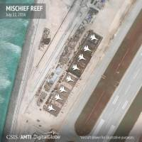 Hangars that the Center for Strategic and International Studies says can hold any Chinese fighter jet are seen on Mischief Reef in the Spratly Islands on July 22. Aircraft have been added for illustrative purposes. | CSIS ASIA MARITIME TRANSPARENCY INITIATIVE / DIGITALGLOBE / VIA REUTERS