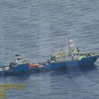 An apparent Chinese vessel is seen near the disputed Scarborough Shoal in the South China Sea in this photo released Wednesday. | PHILIPPINE DEFENSE MINISTRY