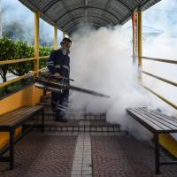 A pest control worker fumigates a school corridor on the eve of the annual national primary school evaluation test in Kuala Lumpur on Sunday. | AFP-JIJI