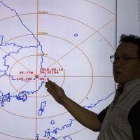 An official from the Korea Meteorological Administration explains an earthquake at the at the National Earthquake and Volcano Center of the Korea Meteorological Administration in Seoul on Monday.   AP