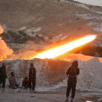 Free Syrian Army fighters launch a Grad rocket from Halfaya town in Hama province, toward forces loyal to Syria's President Bashar aAssad stationed in Zein al-Abidin mountain, Syria, Sunday.   REUTERS