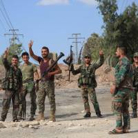 Syrian soldiers gesture Sunday at a location on the southern outskirts of the Syrian city of Aleppo after regime forces retook control of three militaries academies from rebel fighters.   AFP-JIJI