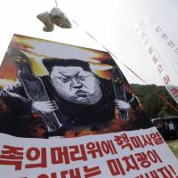North Korean defectors prepare to release balloons carrying leaflets and a banner denouncing North Korean leader Kim Jong Un after the North's latest nuclear test, in Paju, near the border with South Korea, on Sept. 15. | AP