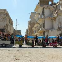 Children ride in carts near damaged buildings during the third day of Eid al-Adha in the rebel controlled city of Idlib, Syria, Wednesday. | REUTERS