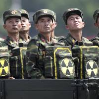 North Korean soldiers carry packs marked with a radiation symbol, possibly to denote tactical nuclear bombs, during a parade on the 60th anniversary of the Korean War armistice in Pyongyang in July 2013. | AP