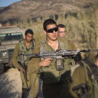 Israeli soldiers secure a road leading to where projectiles fired from Syria hit the Israeli-controlled part of the Golan Heights on Tuesday. | AP