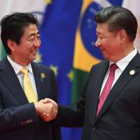Prime Minister Shinzo Abe poses with Chinese President Xi Jinping before the Group of 20 leaders' family photo in Hangzhou, China, on Sunday. World leaders converged on the city for the two-day G-20 leaders' summit. | AFP-JIJI