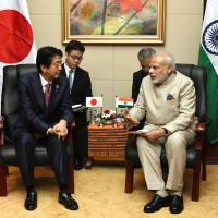 Prime Minister Shinzo Abe and his Indian counterpart, Narendra Modi, hold talks on the sidelines of the Association of Southeast Asian Nations summit in Vientiane on Wednesday. | KYODO