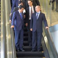 Prime Minister Shinzo Abe and Russian President Vladimir Putin ride down an escalator during their meeting on the sidelines of the Eastern Economic Forum in Vladivostok, Russia, on Friday. | REUTERS