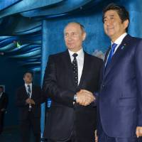 Prime Minister Shinzo Abe shakes hands with Russian President Vladimir Putin while visiting an oceanarium on Russky Island, Russia, on Saturday.         POOL / via AP | AP