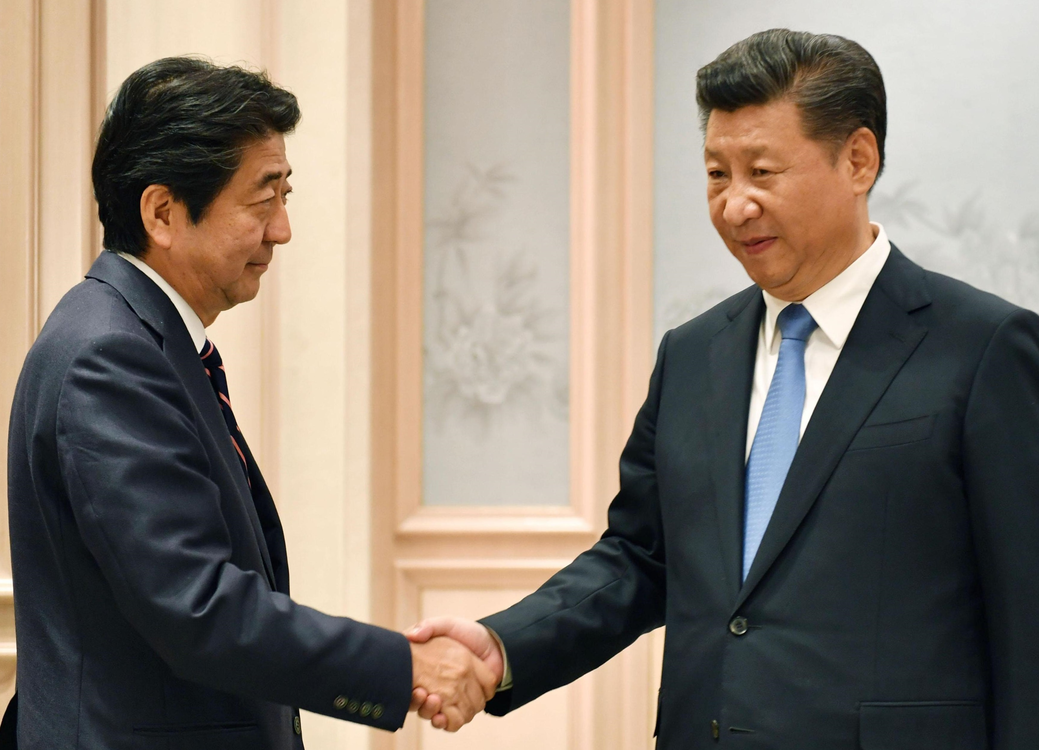 Prime Minister Shinzo Abe and Chinese President Xi Jinping get together for talks after the Group of 20 summit in Hangzhou, China, on Monday. | POOL / VIA KYODO
