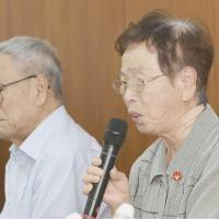 Plaintiff Tsutae Takai speaks at a news conference after a court ruling on Wednesday in Nagoya as fellow plaintiff Toshio Mori looks on. | KYODO